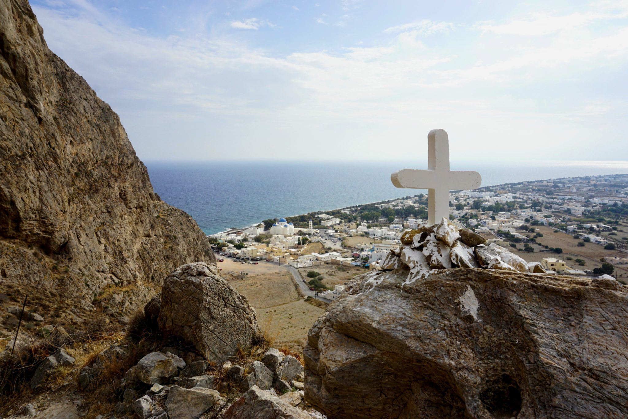 A wooden cross with Perissa in the background.
